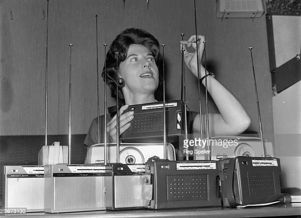 A woman inspects the aerials of Floret transistor radios at the Radio Show at Earl's Court London