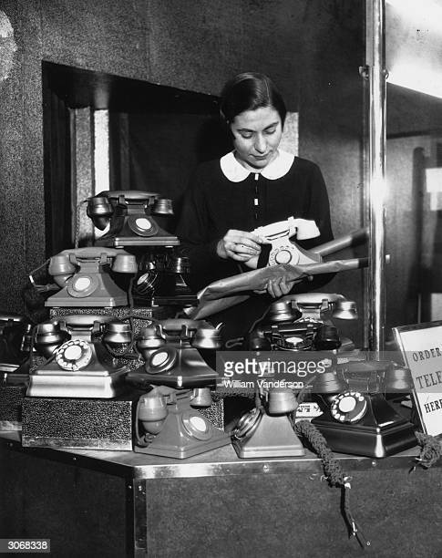 Worker at a GPO export office gift-wraps the new hand-microphone telephones prior to despatch. The Post Office is inviting telephone subscribers to...