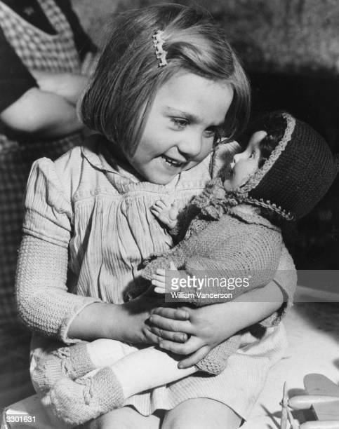 Diana Burl born during the Blitz cuddles a doll one of the gifts distributed through Hoxton Market Mission London from an Australian charity It is...