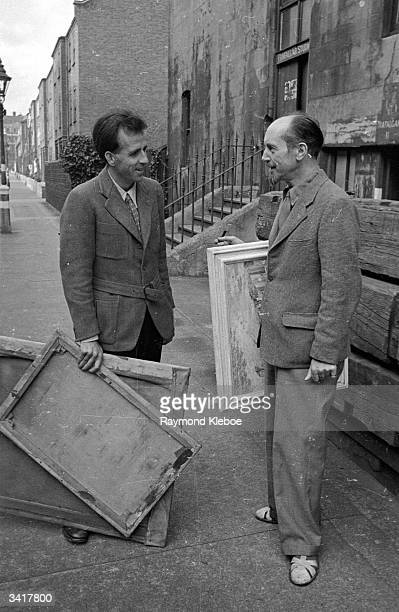 English author and visual artist Mervyn Laurence Peake having a conversation with a fellow artist on a London street Original Publication Picture...