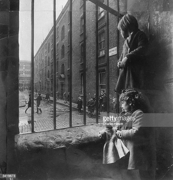Two young children watching others play outside in Christmas street off Old Kent Road in South East London Original Publication Picture Post 4277 The...