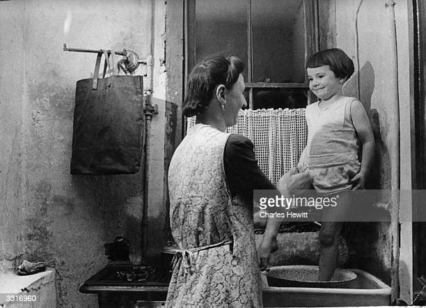 A mother washes her child at the kitchen sink Original Publication Picture Post 4277 The Story Of Christmas Street pub 1947