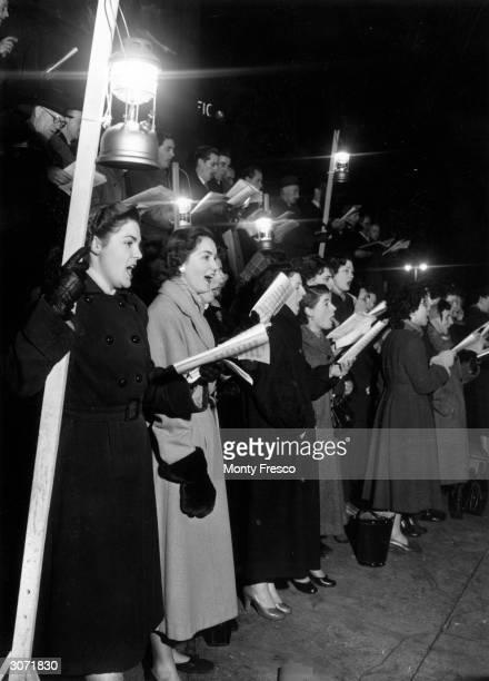 Carol singers around the Christmas tree at Trafalgar Square, London.