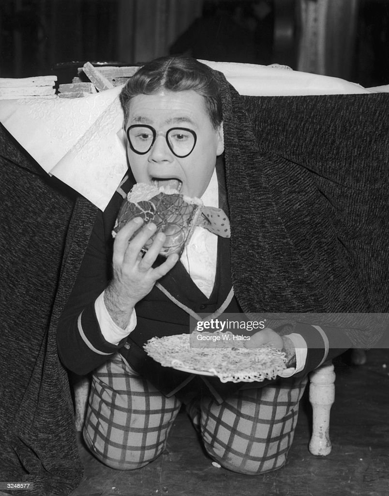 Gerald Campion (1921 - 2002) reprises his television role of the corpulent schoolboy for the pantomime 'Billy Bunter Flies East' at the Victoria Palace, London. A dress rehearsal finds Billy in typical pose, having his cake and eating it under the table.