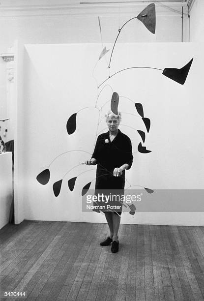 American art collector Peggy Guggenheim touching a mobile sculpture by American artist Alexander Calder at the Tate Galley London