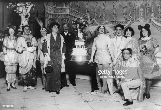 Miss Nora Delaney surrounded by the rest of the cast with a cake made in celebration of her being voted by the public as the 'most charming pantomime...
