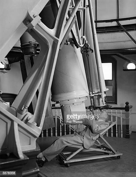 Royal Astronomer Dr Harold Spencer Jones looking through a giant reflecting telescope at Woolwich Observatory London