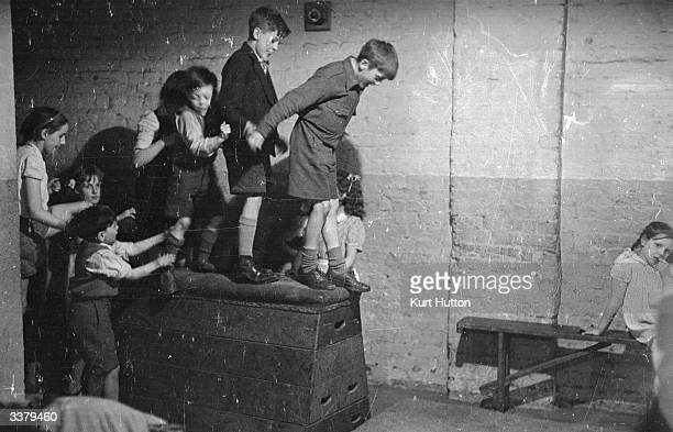 A group of children lining up on the box in the gym at Mansford youth club in Bethnal Green which is supported by the Save The Children Fund Original...