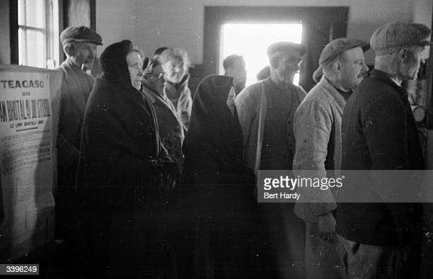 In a schoolhouse corridor the islanders of Innishfeer wait their turn to vote in the 1948 Irish elections A poster gives instructions for filling in...