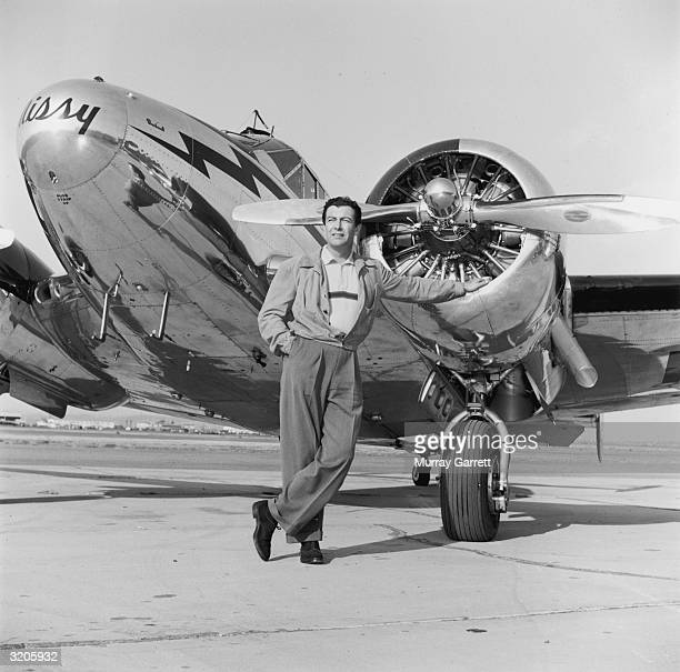 EXCLUSIVE Fulllength image of American actor Robert Taylor leaning against one of the engines of his airplane 'Missy' on the runway of the Santa...