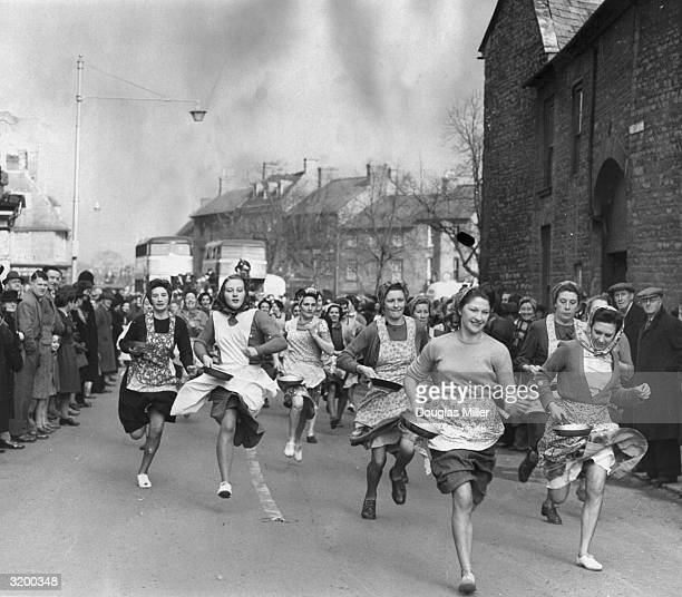 Housewives in Olney Buckinghamshire England competing in a transatlantic pancake race American women took part in a similar race in Liberal Kansas...