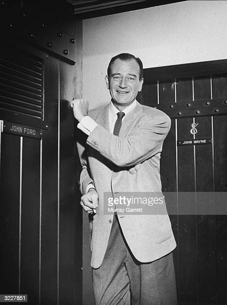 EXCLUSIVE American actor John Wayne smiles and knocks on director John Ford's door at the Republic Pictures Studio offices Hollywood California