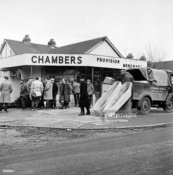 A crowd outside a provision merchant's shop on Canvey Island during flooding beside a couple of coffins leaning on a lorry Original Publication...