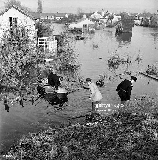 Residents trying to salvage possessions from houses surrounded by floodwater on Canvey Island Original Publication Picture Post 6423 Floods Return To...