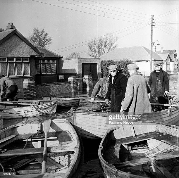 Rowing boats in floodwater in a street on Canvey Island Original Publication Picture Post 6423 Floods Return To Canvey Island One Man's Story pub 1953