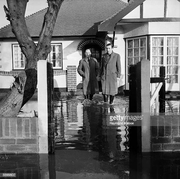 Two men walking away from a bungalow through floodwater on Canvey Island Original Publication Picture Post 6423 Floods Return To Canvey Island One...