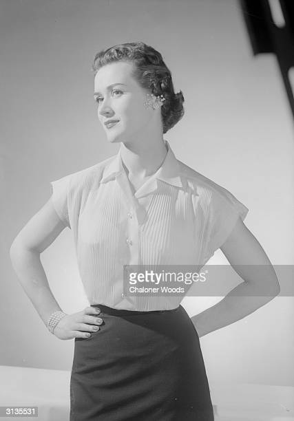 A woman modelling a shortsleeved blouse pleated down the front with pearl buttons and jewellery