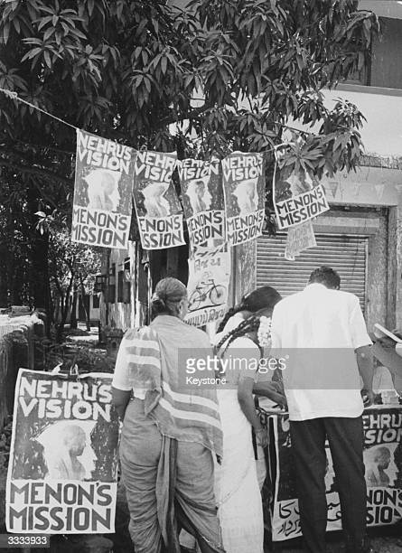 People in Bombay voting in the national election beside posters advertising the political visions of Indian statesmen Pandit Nehru and Krishna Menon
