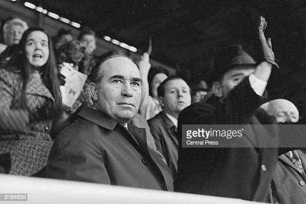 England team manager Sir Alf Ramsey looking grim while others in the crowd cheer as Barry Bridges scores for Queens Park Rangers in an FA Cup Ties...