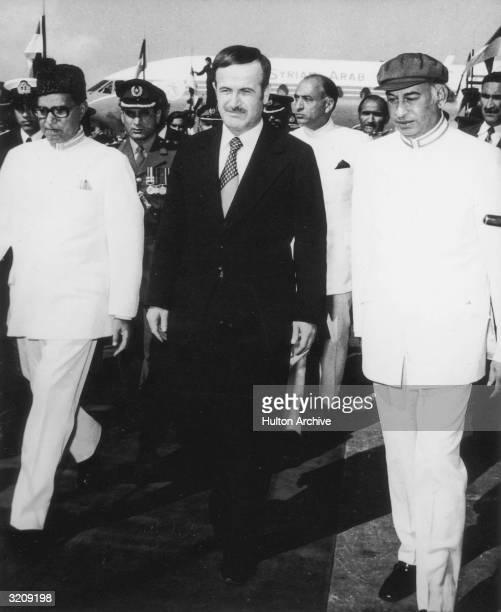 Syrian president Hafez alAssad walks with President Fazal Elahi Chaudhry and Prime Minister Zulfikar Ali Bhutto of Pakistan after his arrival at...