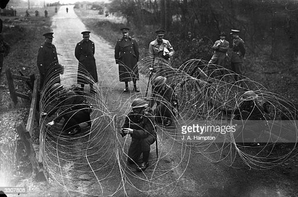Troops of the 1st Battalion South Staffordshire Regiment demonstrating modern infantry equipment by blocking a road with French wire at Aldershot...