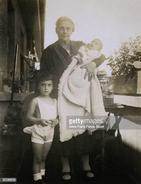 EXCLUSIVE Anne Frank being held by her paternal grandmother Alice FrankStern next to her sister Margot Frank on a balcony Frankfurt am Main Germany...