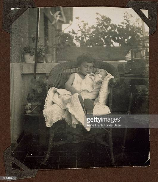 EXCLUSIVE Margot Frank sitting on a wicker chair holding her baby sister Anne Frank in a blanket Frankfurt am Main Germany They are on a balcony From...