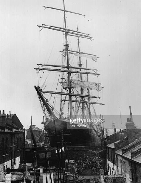 The schooner 'Penang' lying in Millwall Docks has its bow running right through the back gardens of a little street