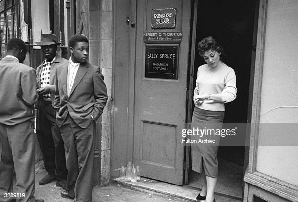 Andria Loran a model in London's Soho democratically elected 'Queen of Soho 1956' stands in the doorway of the Mambo Club keenly noticed by an...