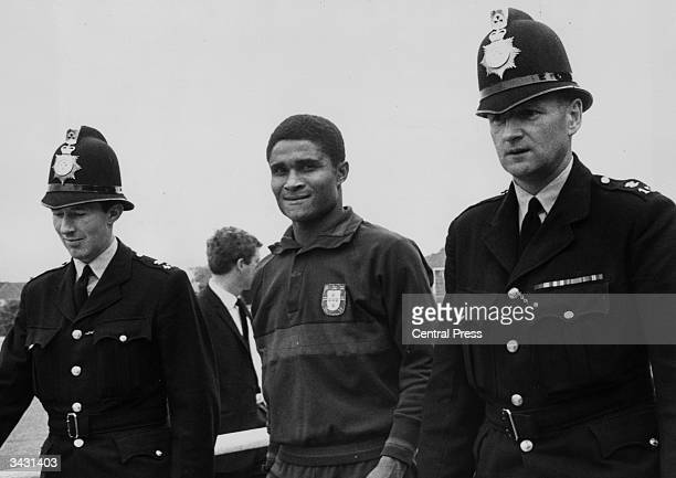 Portuguese footballer Eusebio being escorted by two policemen to protect him from the autograph hunters who follow him everywhere