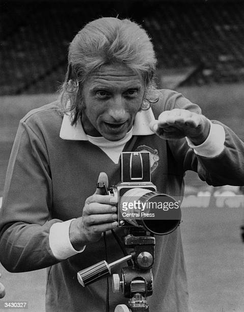 Denis Law the Scottish footballer taking a photograph during a Manchester United training session