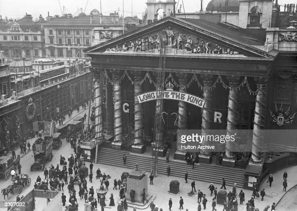 Workmen putting up decorations at the Royal Exchange to celebrate the Coronation of King George V