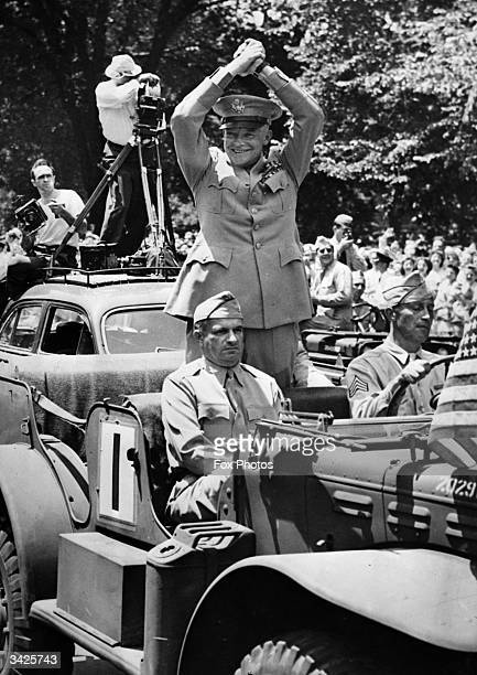 American General Dwight D Eisenhower the Supreme Commander of Allied Forces in Europe acknowledging the crowd as he is driven through the streets of...