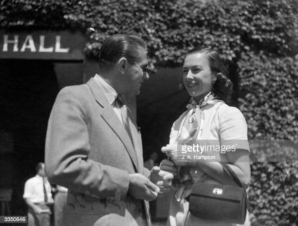 Czech tennis player Jaroslav Drobny chatting with Gertrude 'Gussie' Moran of the USA before their respective games at the Wimbledon Lawn Tennis...
