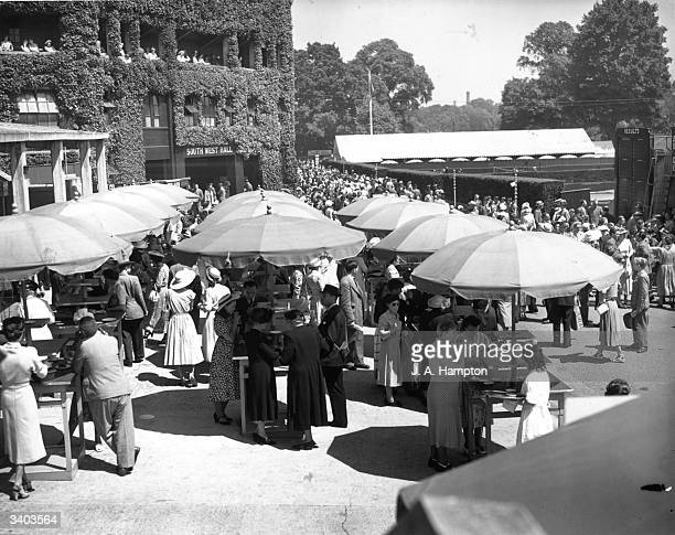 Spectators at the International Lawn Tennis Championships take refreshments under umbrellas at the All England Lawn Tennis Club Wimbledon London