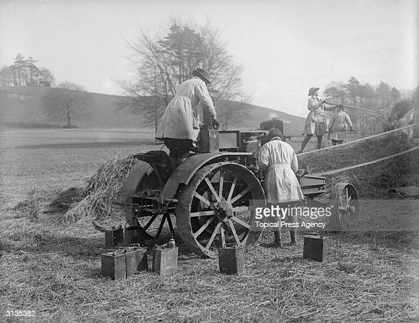 Women during training to be Land Girls are working on agricultural machinery