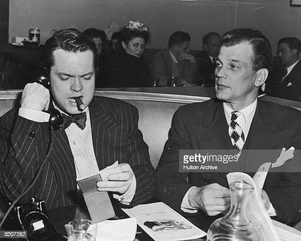 American actor and director Orson Welles and American actor Joseph Cotten sit at a booth in the Brown Derby Restaurant after the Hollywood Victory...