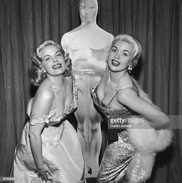 American actors Cleo Moore and Jayne Mansfield display their cleavage while posing in front of an Oscar likeness at the Academy Awards RKO Pantages...
