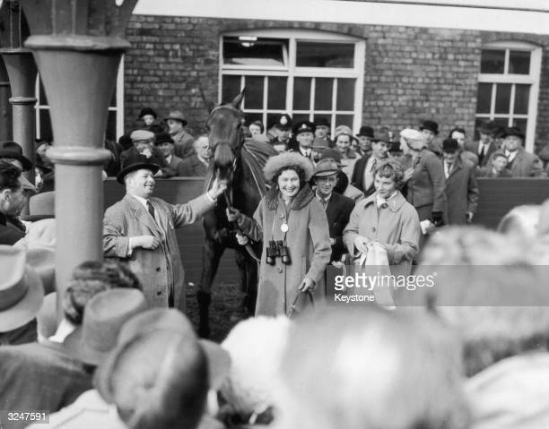 Mr Bigg and his wife, owners of the Grand National winner Oxo, lead the horse to the paddock after its victory at Aintree in Liverpool.