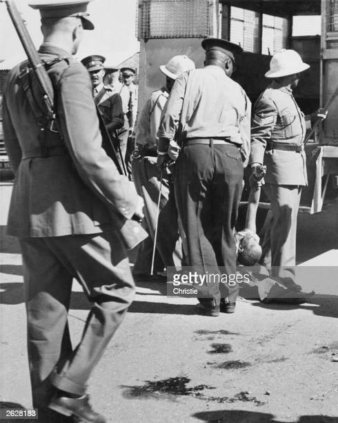 South African police take away the body of a black woman killed during the Sharpeville massacre Police opened fire on a crowd protesting against...