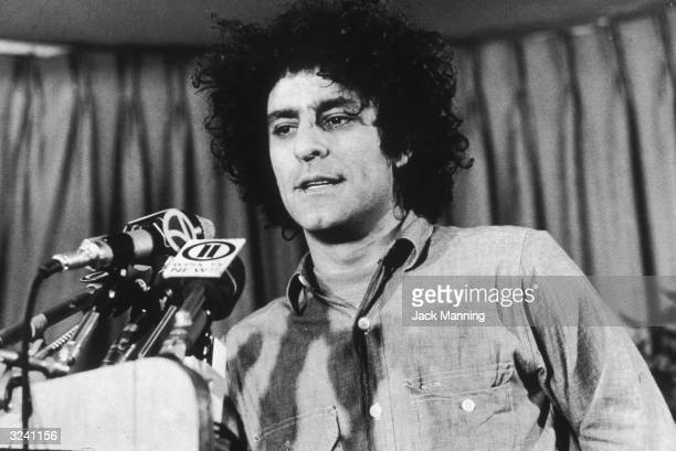 Headshot of American political activist Abbie Hoffman speaking to reporters at a press conference
