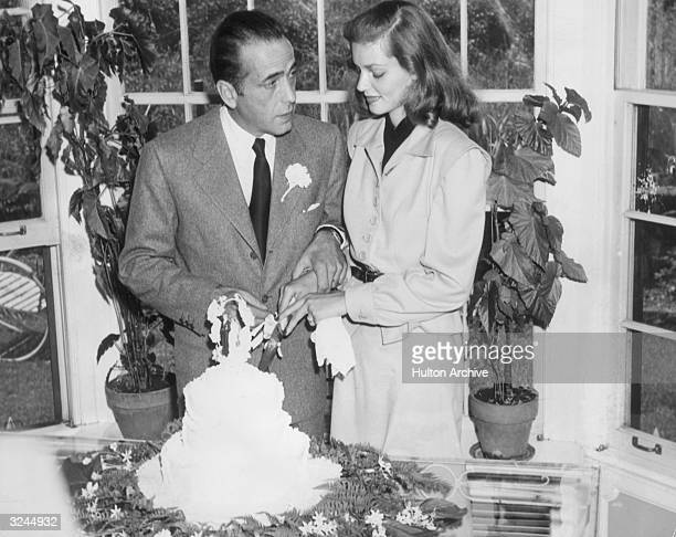 Married American actors Lauren Bacall and Humphrey Bogart cut the cake at their wedding