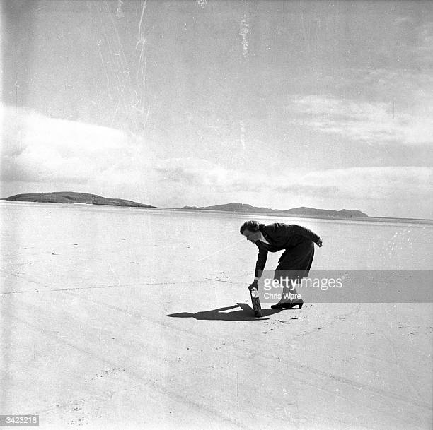 Kitty MacPherson who singlehandedly runs the airport on the tiny Hebridean island of Barra picks up a piece of flotsam from the sandy runway before...