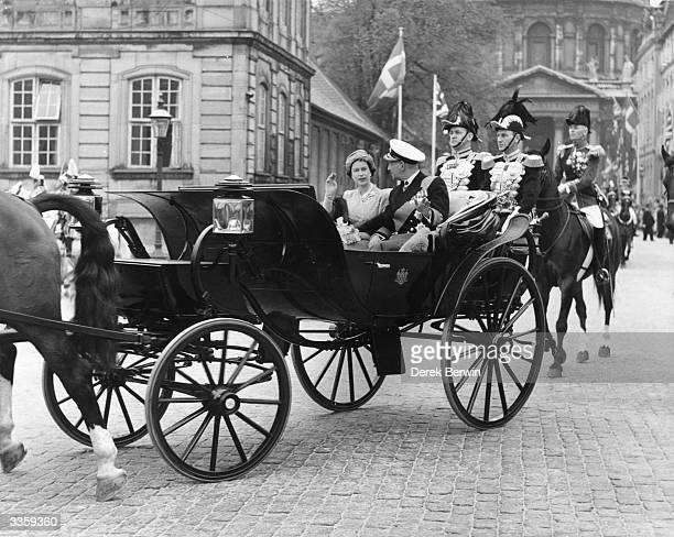 Queen Elizabeth II and King Frederick of Denmark riding through the streets of Copenhagen in an open carriage during her three day visit to Denmark