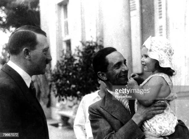 21st November 1934, German Chancellor and Nazi dictator Adolf Hitler, left, chats to his Propaganda Minister Dr, Goebbels who is holding his daughter...