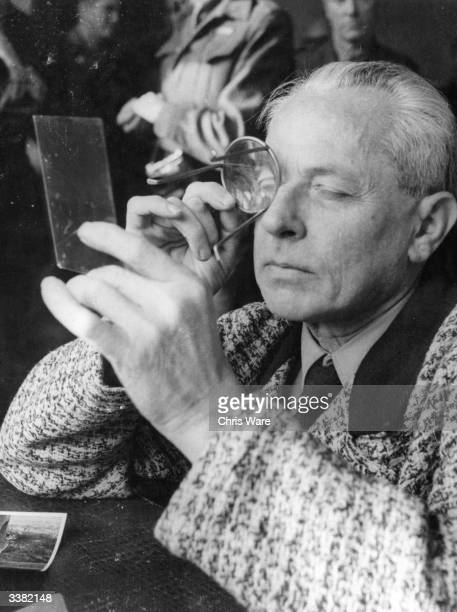 Heinrich Hoffmann Hitler's photographer and confidante of high ranking Nazis examines a negative through a magnifying glass Hoffmann is under open...