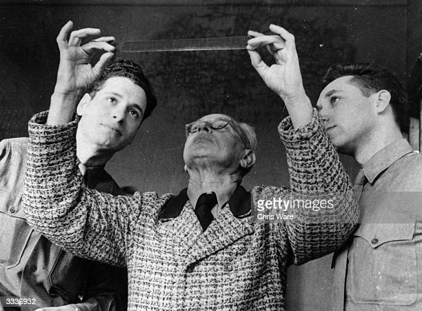 Hitler's photographer Heinrich Hoffmann examining a negative during the Nuremberg Trial accompanied by two American soldiers