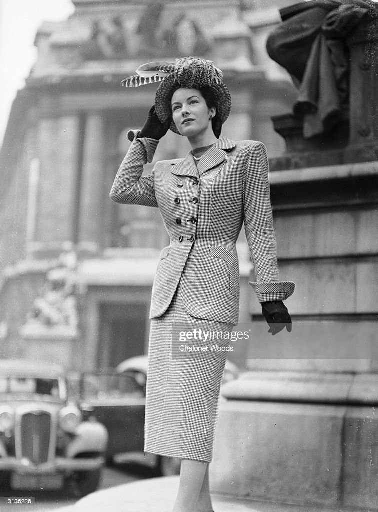 A woman modelling a tailored Simon Massey suit with a feathered hat.