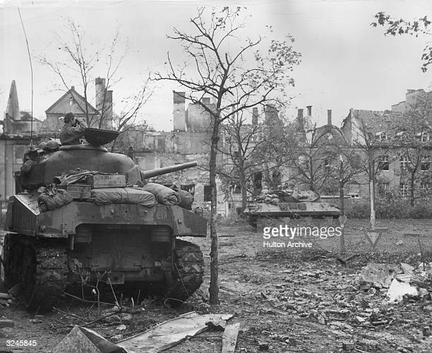 A soldier stands in the turret of a US tank scanning with binoculars as American troops enter Aachen Germany Another tank in the background moves...