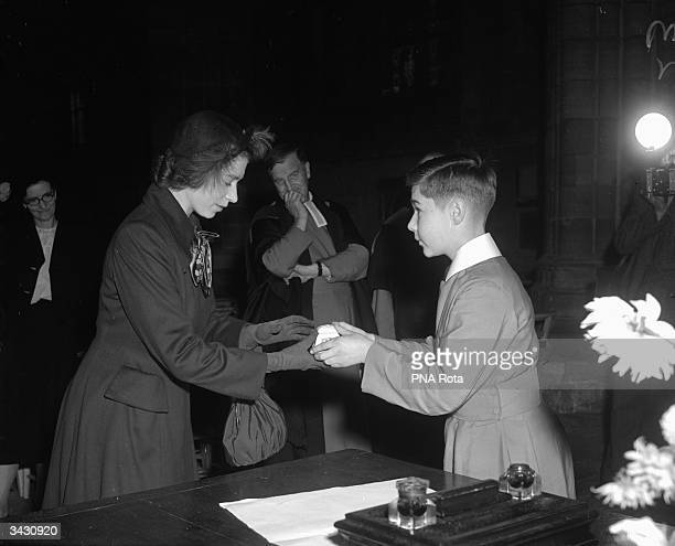 The head choirboy of Exeter Cathedral presents Princess Elizabeth with a stone box on the first day of her royal tour of Devon and Cornwall